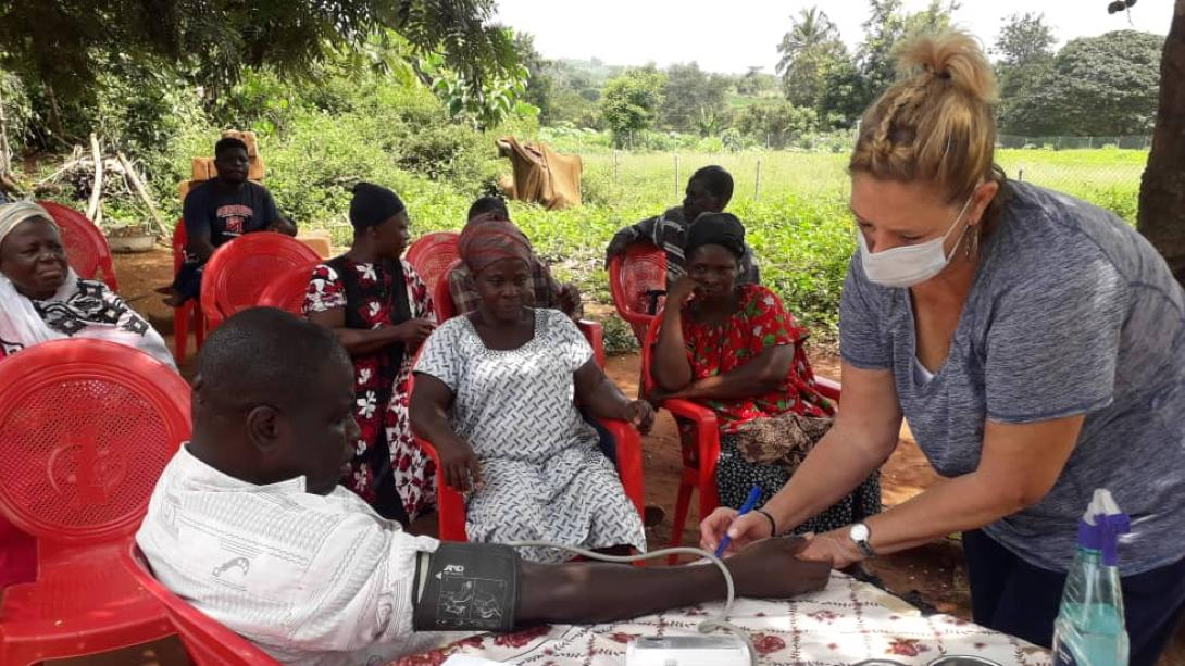 A Projects Abroad volunteer performs basic health checks on locals in Ghana on the Public Health Program